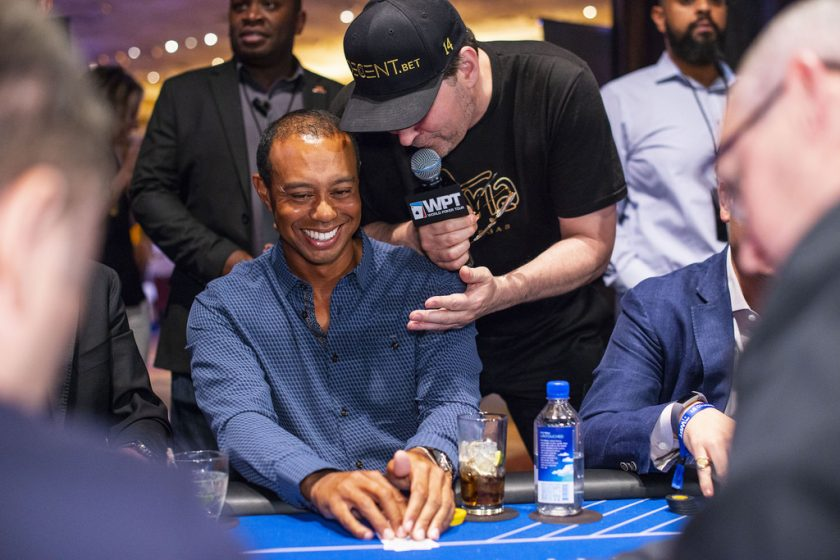 Event emcee Phil Hellmuth checks in on Tiger Woods during play